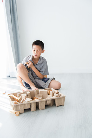 establishes: Asian boy playing a Structure from Wooden Building Blocks with big window and natural light.