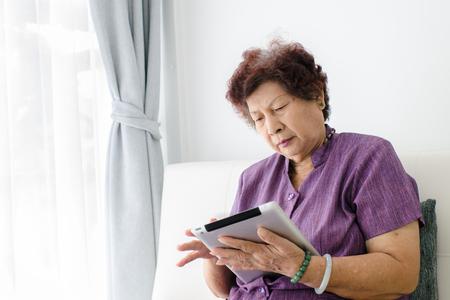 tercera edad: Mujer mayor asiática en casa conectado a Internet