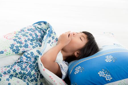 Asian girl  yawning in bed before sleeping Stock Photo