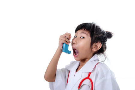 inhaling: Small girl in doctors coat inhaling medicine