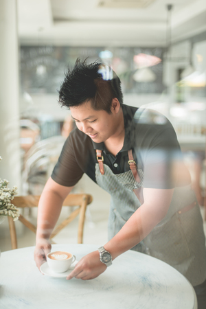 테이블에 커피를 제공하는 바리 스타, 창 반영에서 사진을 가져가 라. 스톡 콘텐츠