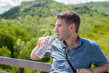 man drinking water: man drinking water from a bottle, outdoor with sunny day.