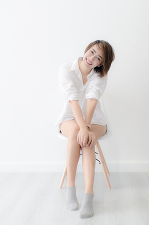 Attractive Asian woman wearing a white shirt sitting on chair at home.
