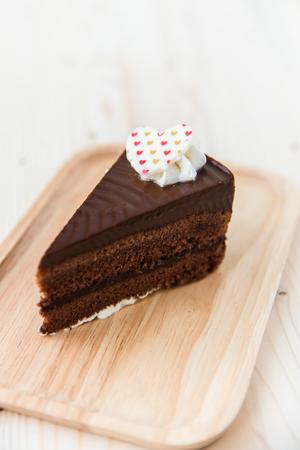 gateau chocolat: Chocolate cake slice on wooden plate.