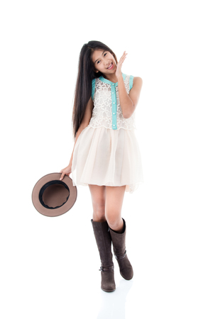 Cute Asian teenager wearing dress and boots on white.