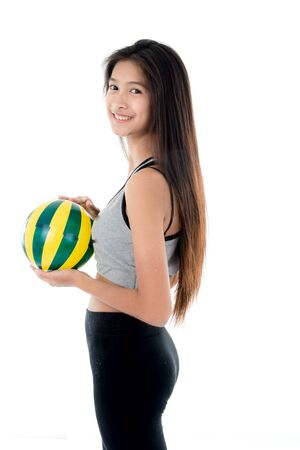 express positivity: Young woman in sports wear holding  ball. All on white background. Stock Photo
