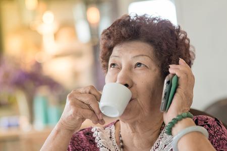 phone calls: Happy Asian senior woman drinking tea at home. Stock Photo