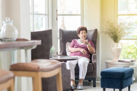 Glückliche asiatische ältere Frau Tee zu Hause zu trinken.