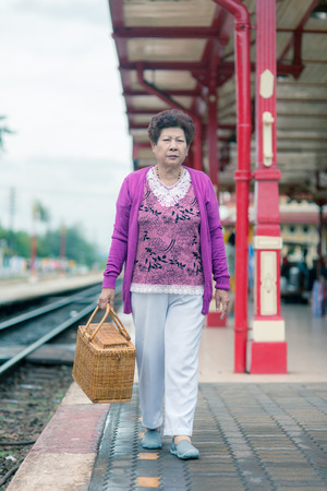 vital: Mature vital elderly woman at the train station. travel on holiday in vintage tone.