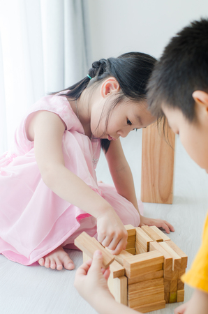 toy house: Asian children playing wooden blocks at home.