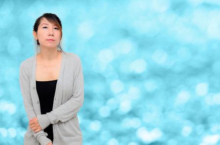 cardigan: Chinese Asian woman Model wearing grey cardigan on blurry blue bokeh background. Stock Photo