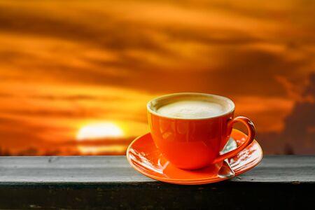 Oranje kopje koffie met zonsopkomst achtergrond. Stockfoto