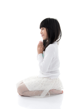 clasped hands: Asian girl praying with clasped hands with blank copy space Stock Photo