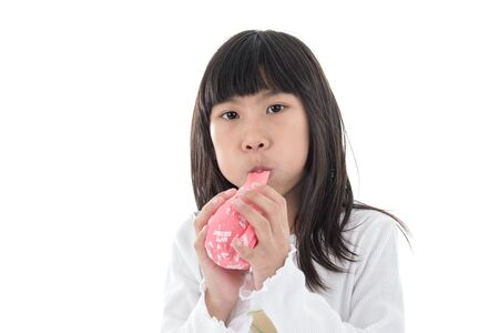 inflate: Little Girl inflate a Pink Balloon with Happy birthday message on the White Background Stock Photo