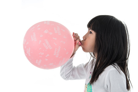 to inflate: Little Girl inflate a Pink Balloon with Happy birthday message on the White Background Stock Photo