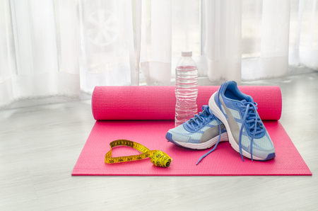 Sport shoes, yoga mat, bottle of water and centimeter on wooden background. Sport equipment. Concept healthy life. Selective focus Archivio Fotografico