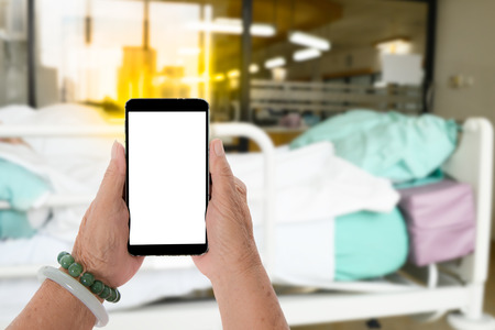 health insurance: Senior hands holding smart phone with blurry hospital room background, health or insurance concept. Stock Photo