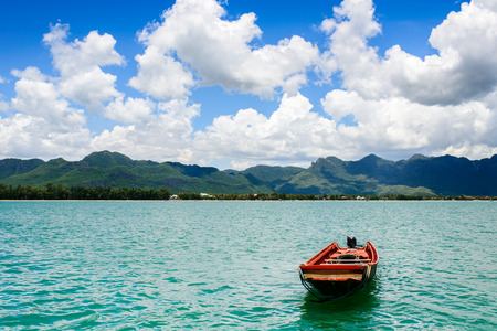 pristine coral reef: Boat on ocean with cloudy and sunny day. Stock Photo