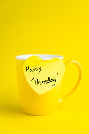 thursday: Happy Thursday message on yellow mug. Stock Photo