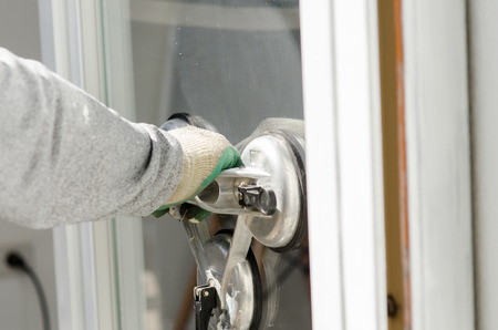 glasscutter: Close up worker with suction cup holding glass in sunny day. Stock Photo
