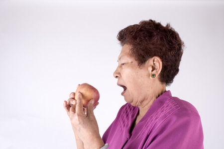 Healthy lifestyle concept. Asian senior woman eating an apple over gray background