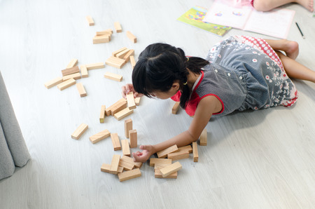 establishes: Asian children playing wooden blocks on floor at home.