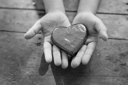 Schwarzweiss-Herz in den Händen des Kindes Standard-Bild - 49211410