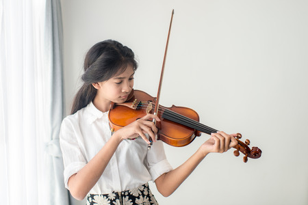 fiddles: Asian teenager playing violin next to window, emotion concept. Stock Photo