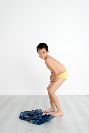 Asian shy boy with underwear on gray background.