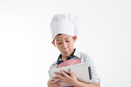 asian cook: Young Asian Cook Touching Tablet Isolated on gray background. Stock Photo