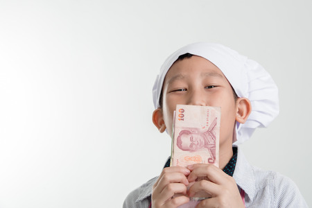 asian cook: Young Asian cook holding Thai Baht in his hand and kissing.