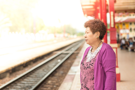 vital: Mature vital elderly woman at Hua Hin train station. travel on holiday in vintage tone.