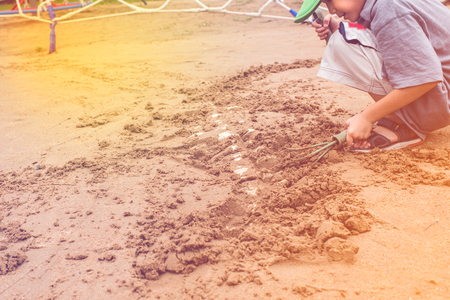 Asian boy have fun digging in the sand at adventure park Stockfoto