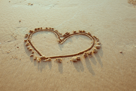 evoke: Heart drawn on sand. Horizontal composition. Stock Photo