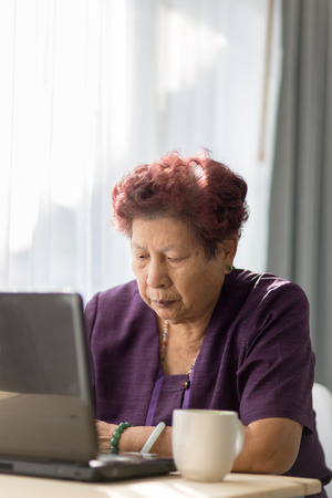 websurfing: Asian senior woman learning notebook and drink a cup of tea at home.