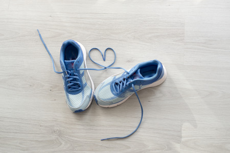 gym floor: Love sign, Selective focus close up blue sport shoes on gray floor.