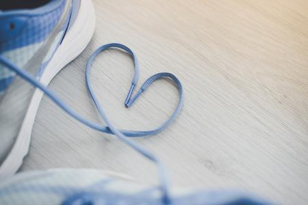Muestra del amor, de enfoque selectivo de cerca los zapatos de deporte azul en el suelo gris.
