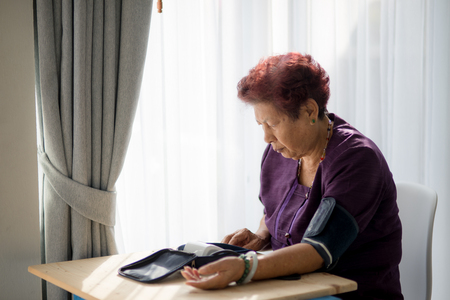blood sugar count: asian senior woman checking blood pressure with window light Stock Photo