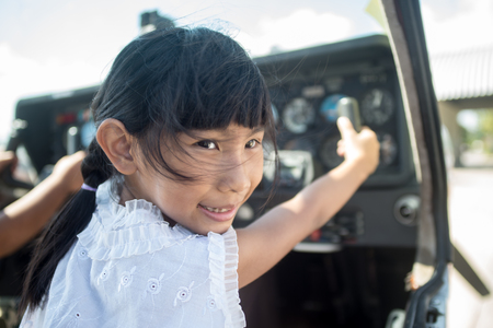 Asian girl in cockpit of plane with sunny day. Stock Photo