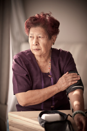 blood sugar count: Asian senior woman checking blood pressure with window light and vintage tone