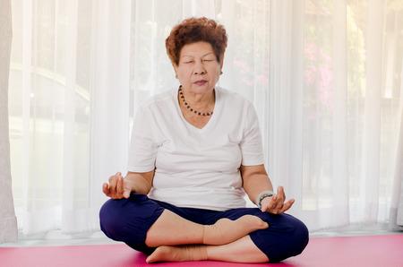yoga pillows: Senior woman making meditating at home.