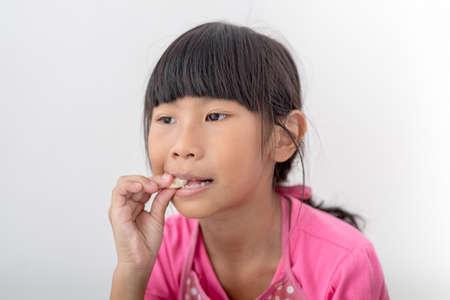 comiendo pan: Muchacha asiática que come el pan en casa.