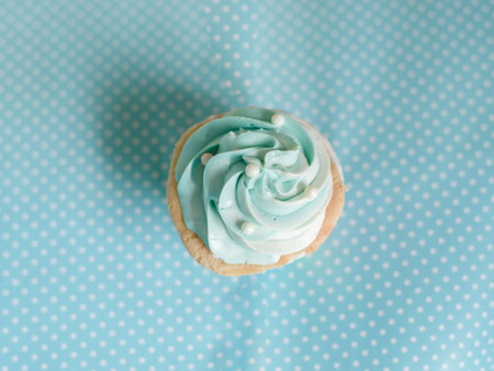 butter icing: Pearl birthday cupcake with butter cream icing on blue pastel background. Stock Photo