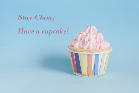 butter icing: Pearl birthday cupcake with butter cream icing on blue pastel background.  Stay clam, have a cupcake. Stock Photo
