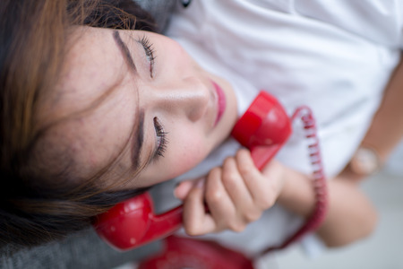 25 30 years: Young Asian woman laying on couch talking on red retro telephone Stock Photo