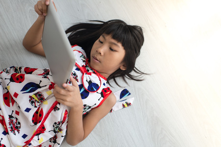 top 7: Child with tablet lying on floor. Girl playing laptop computer Stock Photo