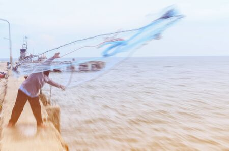 fishing pier: motion blur fisherman casting his net from the boat at Hua Hin fishing pier. Stock Photo