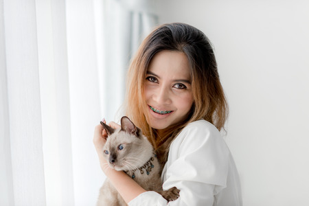 cute pussy: beautiful smiling Asian girl holding her cat with window light at home.