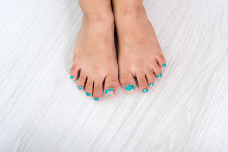 grey nails: Children painting toe nails  pedicure on grey background. Stock Photo