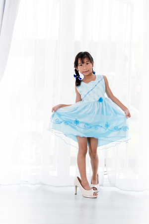 Motion blur Asian girl dancing and wearing her mothers shoes  at home. Stock Photo